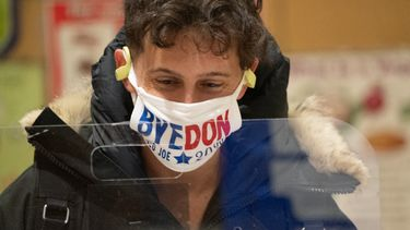 Een foto van een Amerikaan die stemt met een mondkapje met de tekst Bye Don