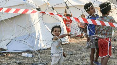 Op deze foto zijn drie kinderen in een vluchtelingenkamp te zien.
