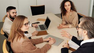mensen kijken naar leidinggevende aan tafel