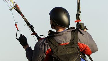 Paraglider raakt in de knoop en zit urenlang vast in elektrische draden