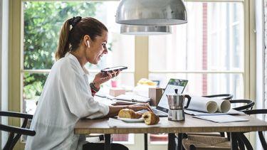 Een foto van een vrouw die haar werk thuis aan tafel doet