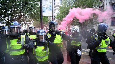 Een foto van politie in zware uitrustig op de straten van Londen, er hangt een roze gaswolk achter ze.