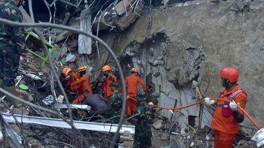 Een foto van reddingswerkers in de puinhopen van Indonesië