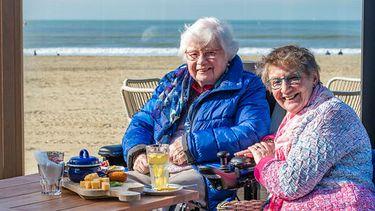 Op deze foto zie je een medewerker van de Zonnebloem aan het strand samen met een oudere persoon in een rolstoel. Dankzij rolstoelauto kan Magda uitwaaien op het strand.