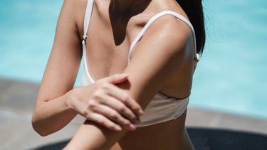 vrouw smeert zich in met zonnebrandcreme
