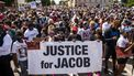 Op deze foto zijn mensen in Kenosha te zien, terwijl ze protesteren tegen politiegeweld. Ze houden een spandoek vast met 'Justice for Jacob' erop.