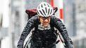 een foto van een fietsende man in de regen