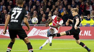 Een foto van voetballers die hard bezig zijn, een man in het zwart schopt de bal net weg voor een man in het rood-wit erbij kan