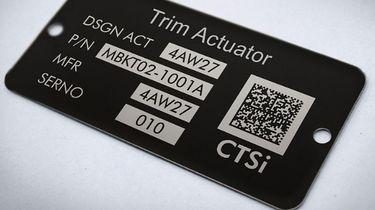 Een foto van een zwart bordje met naam en qr-code