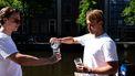 Een foto van twee mannen van Aquablue die Amsterdams grachtenwater drinken.