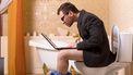 Een foto van een man op het toilet terwijl hij op zijn laptop werkt