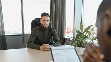 man stelt zelf vragen tijdens sollicitatiegesprek