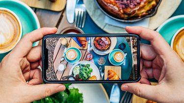 Op deze foto zie je hoe een influencer een foto maakt van zijn eten