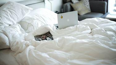 Een laptop op een bed.