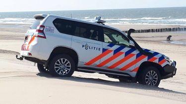 Op deze foto is een politieauto te zien op het strand waar de cocaïne was aangespoeld.