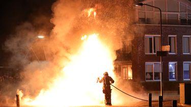 Een lid van de brandweer blust een brand.