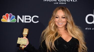 Op deze foto is Mariah Carey te zien, ze houdt een trofee vast.