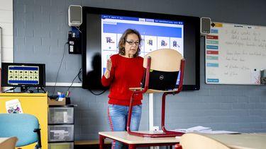 Een foto waarop een lerares digitale lessen geeft op afstand