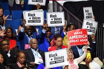 Een foto van publiek met bordjes met de tekst Black Voices for Trump