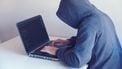 Man met hoodie achter een laptop