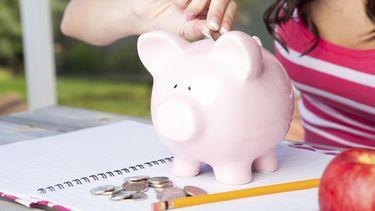 Op deze foto zie je een student die geld in een spaarvarken doet