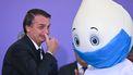 Een foto van de president van Brazilië met een mascotte voor het coronavaccin