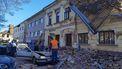Een gebouw is beschadigd, een auto bedolven onder puin.