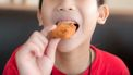 Een foto van een kipnugget in de mond van een jongetje