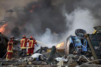 Op deze foto zie je brandweermannen aan het werk om brand te blussen als gevolg van de explosie in Beiroet