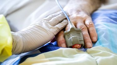 Een foto van een hand van een verpleegkundige op de hand van een coronapatiënt