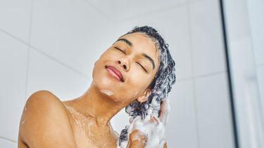 Een foto van een vrouw onder de douche die haar haar wast