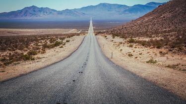 Op deze foto is Death Valley te zien, een lange autoweg met woestijn aan beide zijden.