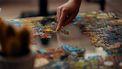 Een foto van een iemand die aan het puzzelen is.