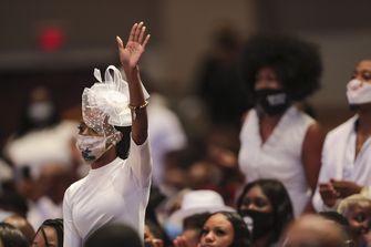 Een foto van een vrouw in het wit die haar hand opsteekt tijdens de begrafenisdienst van George Floyd