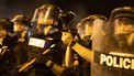 Op deze foto zie je politiemannen die vechten tegen betogers