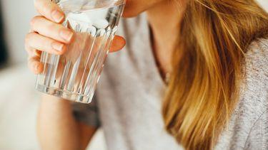 Iemand drinkt een glas water.
