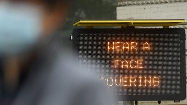 Op deze foto is een bord te zien met daarop 'wear a face covering'.