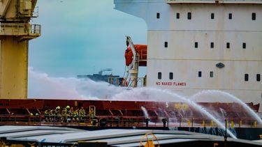 Een foto van een schip waarop door brandweerlieden geblust wordt