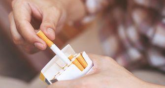 iemand die een sigaret uit een pakje pakt