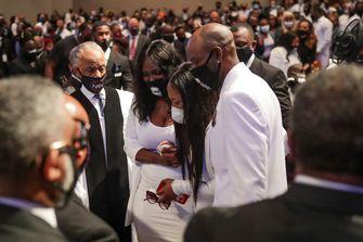 Een foto van rouwende mensen bij de begrafenisdienst van George Floyd.