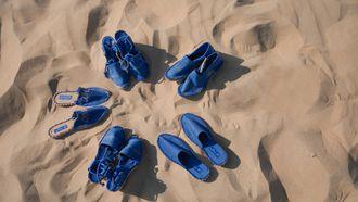 Op deze foto zijn vijf paar schoenen te zien, allen gemaakt van blauwe treinstoelbekleding.