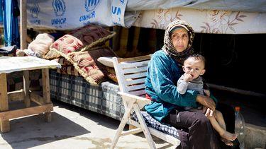Op deze foto zie je een Syrische vluchtelinge met haar kind op schoot voor een tent.