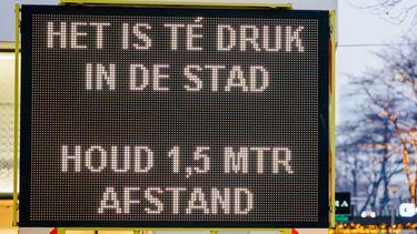 Een bord met 'Het is te druk in de stad, houd 1,5 meter afstand'.