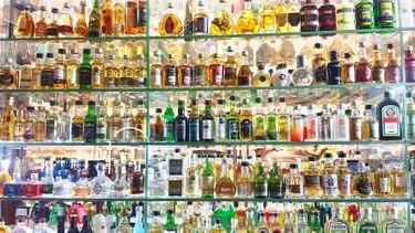 Op deze foto zie je allemaal flessen drank ik een bar in een vitrine.