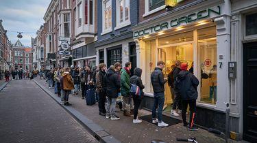Op deze foto zijn mensen te zien die in de rij staan bij een coffeeshop.