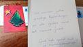 Een foto van een rode kerstkaart met een groene gestileerde kerstboom en een ster erop. In de kaart staat 'We wensen jullie gezellige feestdagen en alle goed voor het nieuwe jaar. Gaat het goed met je zwangerschap?'
