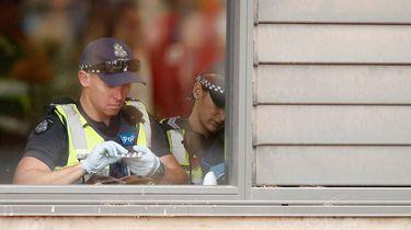 Op deze foto zie je politie in Australie tijdens een festival iemands pillen uit een tas controleren.