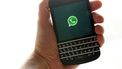 Een foto van een hand met een smartphone waarop WhatsApp te zien is