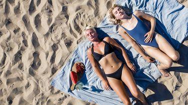Een foto van twee zonnende dames op het strand van Scheveningen