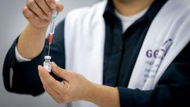 Iemand steekt een injectienaald in een coronavaccin.